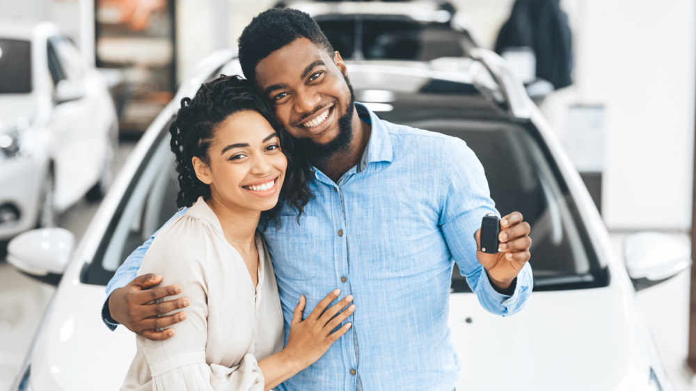 happy young couple buying new car